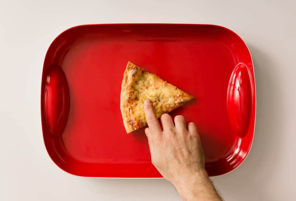 Play button made of pizza cut on red tray